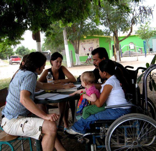 Rigo y Virginia (con el hijo de Virginia, José Carlos) enseñan Español a visitantes voluntarios en PROJIMO. Las clases de Español se crearon para generar ingresos tanto para el programa como para los instructores discapacitados.