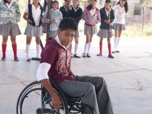 Un niño escolar, Jorge, trata de montar en una silla de ruedas.