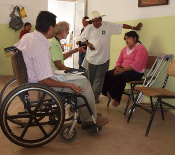 Rigo y David hablan de las posibilidades de rehabilitación que tiene Minerva, una niña con pies zambos. Se diseñará una silla de ruedas para ella en el taller de sillas de ruedas en el pueblo de Duranguito.
