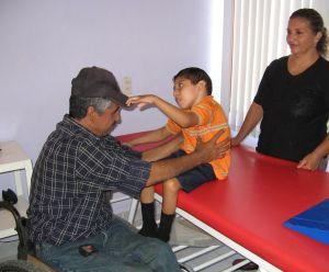 Raymundo Hernandez – quien es una persona con paraplejía y dirige el taller de sillas de ruedas en Duranguito – evalua a un niño para una silla. Rigo coopera con el taller en la identificación de niños que necesitan sillas de ruedas especiales.