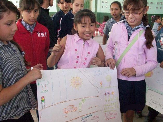 Niños en unos de los programas de Rigo muestran sus pósteres sobre la prevención de accidentes.