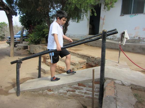 Esta rampa, construida por el abuelo de Tonio, da al niño una mayor independencia para llegar a su casa. Palos de madera envueltos con tubería de riego de plástico evita que se pudran y que duren más.