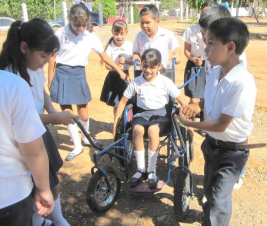 """Todos los niños estaban ansiosos por probar y empujar la nueva """"silla de ruedas-araña"""" de Tonio."""
