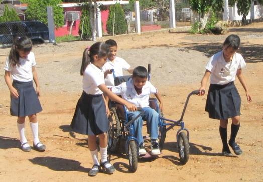 Este niño logra a empujar la silla agarrando los aros fijados contra las ruedas.