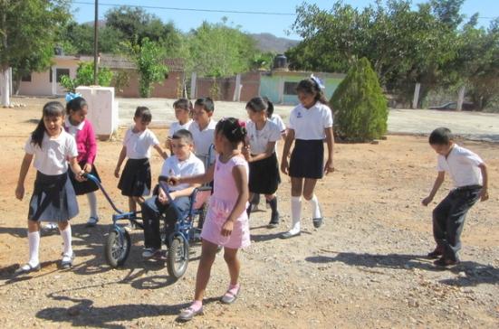 Tonio se sentó en su nueva silla y dejó que sus compañeros le dieran vueltas alrededor del patio de recreo.