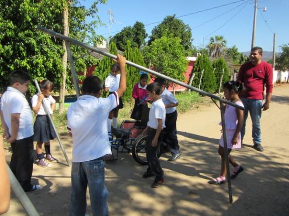 Los niños descargan los tubos soldados para los pasamanos. (Los tubos fueron traídos de Duranguito al mismo tiempo que trajeron la silla de ruedas de Tonio.)
