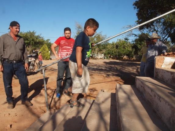 Probando la altura, un niño de más o menos la misma estatura de Tonio sube los escalones.