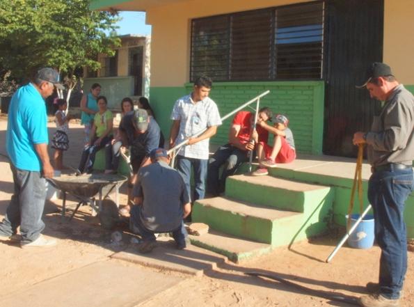 La escuela suministró restos de cemento, arena y grava de un proyecto anterior. Alguien trajo una carretilla para mezclar el concreto; los postes se nivelaron verticalmente.