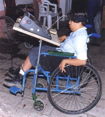 The adjustable table on this wheelchair allows Martha, who has spastic cerebral palsy, to figure out the best position for her computer with her head-stick.