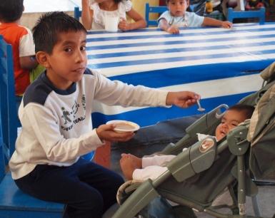 Pacientemente, Benigno ayuda a alimentar a uno de los niños más pequeños.