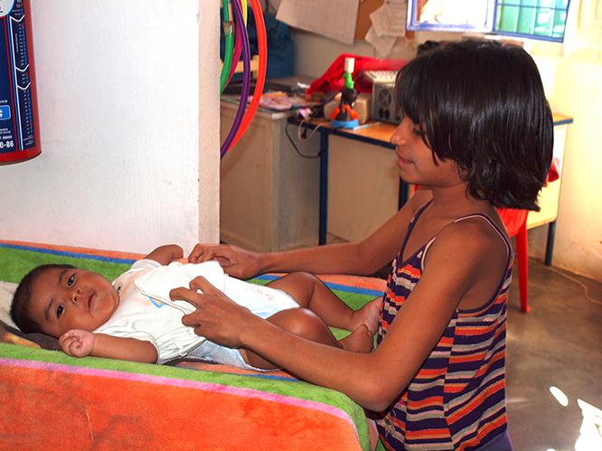 Una niña cambiando los pañales de un recién llegado al refugio.