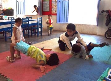 Los niños se ayudan unos a otros con la terapia y los ejercicios. Aquí Benigno ayuda a preparase a Luis para caminar, mientras dos de las niñas hacen sus ejercicios