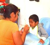 Cuando él llegó a la Casa Hogar a los 3 años de edad, Luis no podía hablar, caminar o comer solo. Aquí la hija de Coco lo alimenta.