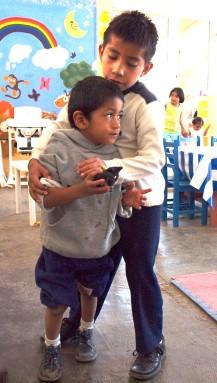 Con la buena disposición de Benigno para ayudar a otros niños. Luis está aprendiendo a caminar.