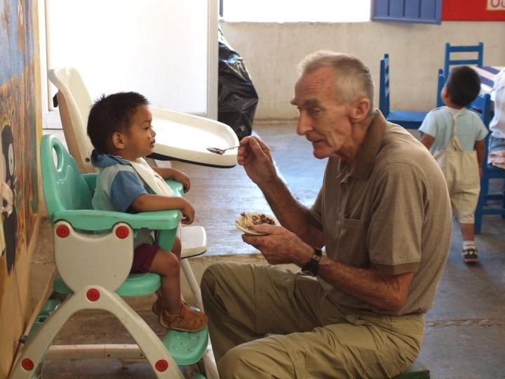 Quienes visitan Hijos de la Luna se contagian del espíritu comunitario y gozan ayudando en lo que pueden. Aquí mi amigo Peter Morris, quien me trajo a Hijos de la Luna, ayudando a alimentar a un infante.