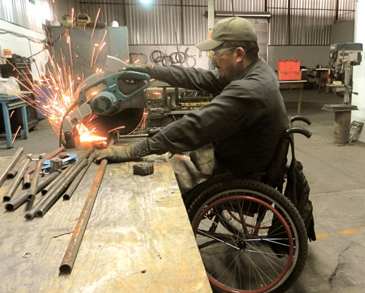 Gabriel in the ARSOBO workshop – cutting tubes to make a wheelchair