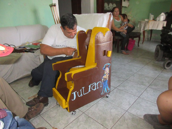 Sergio add final touches to the seat of Julian, a boy with cerebral palsy.