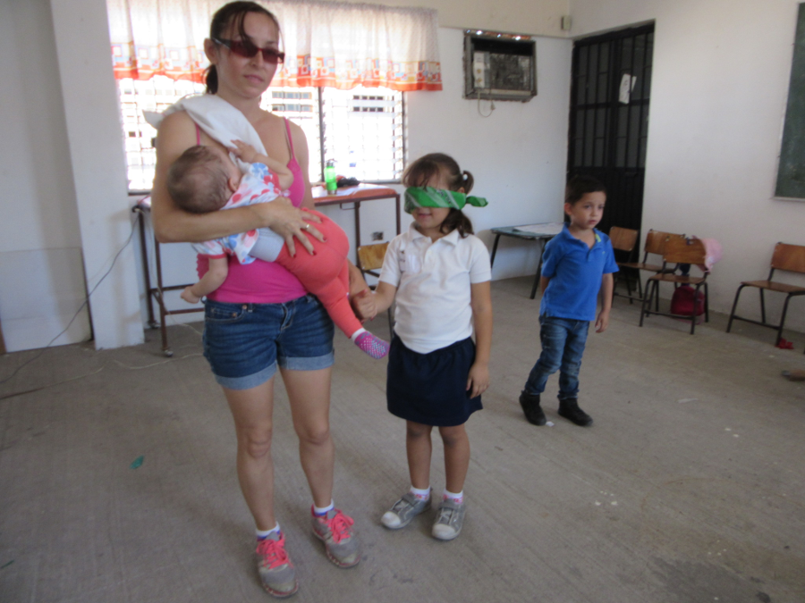 mother leads her blindfolded child to simulate blindness