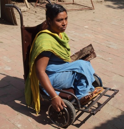 This low-rider wheelchair, made in the Center for Rehabilitation of the Paralyzed in Savar, is adapted for ground-level cooking. The young woman is head of the GK tailoring shop.